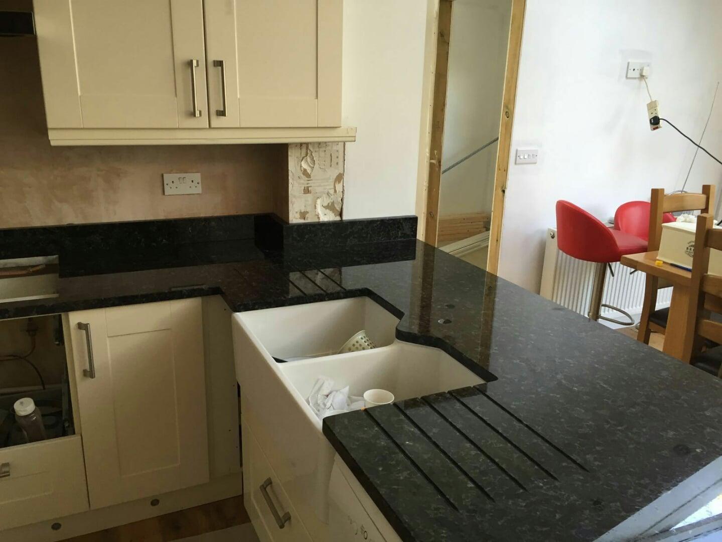 Kitchen sink with matching black glass tap landing and sliding cover - Volga Blue Granite Worktops