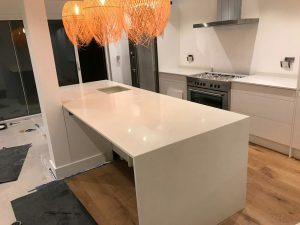 bianco nevoso white quartz island in white kitchen