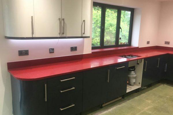 rosso stella red starlight quartz worktops in grey kitchen